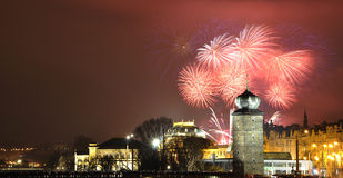 New year fireworks. Celebrating New Year with fireworks exploding over historic city, red sky background stock photo