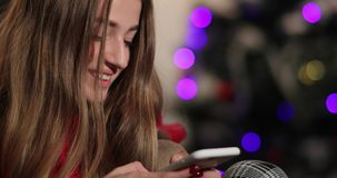 New Year celebration. Charming young woman in red sweater sits on the couch before a Christmas tree and chat with stock footage