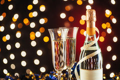 New Year Celebration. Christmas and New Year celebration with champagne. Pair of flute and bottle of Champagne for festive occasions against a dark background Royalty Free Stock Photo
