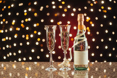 New Year Celebration. Christmas and New Year celebration with champagne. Pair of flute and bottle of Champagne for festive occasions against a dark background Royalty Free Stock Image