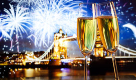 New Year celebration in the city. Champagne glasses and Tower bridge with fireworks in the background stock image