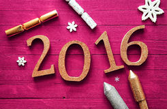 2016 New Year Celebration Design on Table. Simple 2016 New Year Celebration Design on a Wooden Magenta Table with Firecrackers and Snowflakes Stock Photography