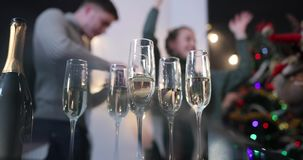 New Year celebration. People dance on the background while camera focuses on the champagne flutes stock footage