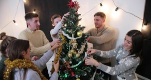 New Year celebration. Three young couples get Christmas tree ready for the party. 4k stock footage