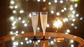 New Year Celebration with two champagne glasses and sparkler. New Year Celebration with two champagne glasses with bokeh lights background stock video