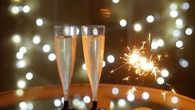 New Year Celebration with two champagne glasses and sparkler. New Year Celebration with two champagne glasses with bokeh lights background stock video footage