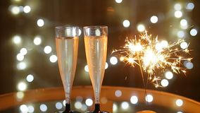 New Year Celebration with two champagne glasses and sparkler. New Year Celebration with two champagne glasses with bokeh lights background stock footage