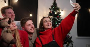 New Year celebration. Two young couples taker a selfie on the smartphone sitting before a Christmas tree stock video