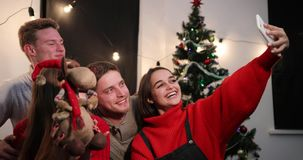 New Year celebration. Two young couples taker a selfie on the smartphone sitting before a Christmas tree stock footage