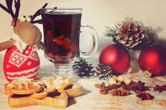 New Year celebratory table with mulled wine, ingredients and cookies, toy deer and Christmas decorations nearby Royalty Free Stock Photos