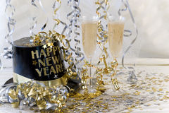 New Year Champagne. Silver and gold themed New Years celebration table with champagne filled glasses, ribbons, stars and New Year party hat stock photos