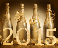 2015 New Year champagne background celebration. With four elegant frosted gold bottles decorated with ribbon above the date 2015 in golden numbers on a Stock Images