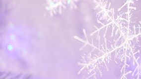 New year and chrismas tree decoration in a shape of a snowflake with light purple backgroung blur. 1:15 stock video footage