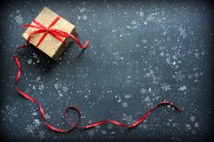 Box with red ribbon on black background with falling snow and snowflakes. Congratulations on the new year and Christmas. New year and Christmas background. Box royalty free stock photos
