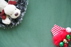 New Year`s tinsel, balls, a red cap, a toy dog on a green background. Place for the inscription. royalty free stock photos