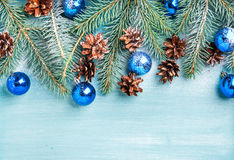 New Year or Christmas background: fir branches, blue glass balls and pine cones over turquoise wooden backdrop, copy Stock Images