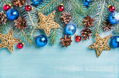 New Year or Christmas background: fir branches, colorful glass balls, cones and golden stars over blue painted wooden Stock Photos