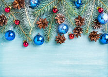 New Year or Christmas background: fir branches, colorful glass balls, cones over blue painted wooden backdrop, copy Stock Image