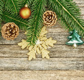 New Year or Christmas background: fir branches, colorful glass balls and golden snow-flake, cones over old wooden backdrop Royalty Free Stock Photo