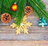 New Year or Christmas background: fir branches, colorful glass balls and golden snow-flake, cones over old wooden backdrop Royalty Free Stock Image