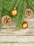 New Year or Christmas background: fir branches, goldish glass balls cones over old wooden backdrop, top view Royalty Free Stock Images
