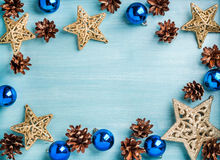 New Year or Christmas background: golden stars, blue glass balls and cones over turquoise wooden backdrop, copy space Stock Image