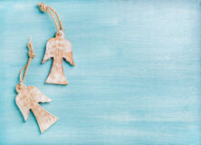 New Year or Christmas background: two wooden angels over blue painted backdrop, copy space royalty free stock photography
