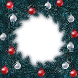 New Year Christmas. Blue branch of spruce in a circle with silver and red balls on a white background. Isolated Stock Photography