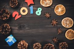 New year or christmas card with 2018 numbers, anise stars, gift-box, dried orange and cones on dark wooden background. Stock Images