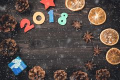 New year or christmas card with 2018 numbers, anise stars, gift-box, dried orange and cones with snow on dark wooden background. Stock Images