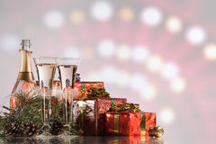 New Year and Christmas celebration. Champagne, two wine glasses, fireworks and gifts Stock Photo