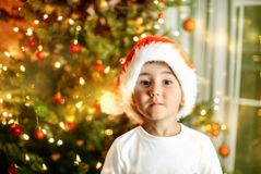 New Year and Christmas child portrait. Emotional face of a boy waiting for Christmas. standing in front of a lightened Christmas tree Stock Images