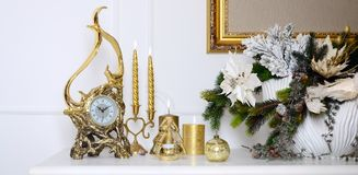 New Year and Christmas composition. Decorative golden clock, thick candles, candlestick, pot of flowers and framed canvas that han stock image