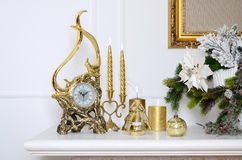 New Year and Christmas composition. Decorative golden clock, thick candles, candlestick, pot of flowers and framed canvas that han royalty free stock photography