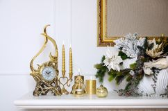 New Year and Christmas composition. Decorative golden clock, thick candles, candlestick, pot of flowers and framed canvas that han royalty free stock images