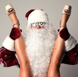 Bad santa claus in snow flakes sunglasses honding young sexy naked legs woman Royalty Free Stock Photography