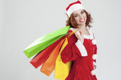 New Year and Christmas Concept and Ideas. Portrait of Laughing C. Aucasian Red-Haired Santa Girl with Shopping Bags. Against White Background.Horizontal Image Royalty Free Stock Photos