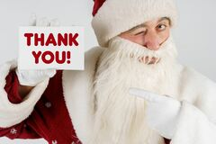 Santa Claus holds a card with the text in his hands - THANK YOU