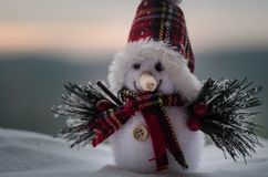 New Year Christmas concept. The snowman stands on snow with blurred nature background. White snowman surrounded by Christmas trees. On evening background. Toy Royalty Free Stock Photography