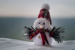 New Year Christmas concept. The snowman stands on snow with blurred nature background. White snowman surrounded by Christmas trees. On evening background. Toy Royalty Free Stock Photo