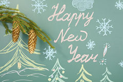 New Year. Christmas decoration from branch of spruce with golden cones on background of blackboard with title HAPPY NEW YEAR Royalty Free Stock Images