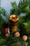 New Year and Christmas decoration. Decorative Christmas and New Year detail with golden candle, walnuts and green branches Stock Image