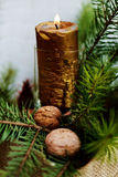 New Year and Christmas decoration. Christmas and New Year still life with golden candle, walnuts and green branches Stock Photo
