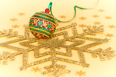 New Year 2015 decoration. Christmas handmade colorful ball. Snowflakes, ribbon on golden background Royalty Free Stock Image