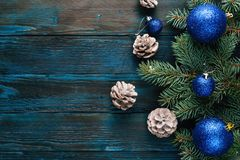 New Year and Christmas decorations Pine tree branches, cones, blue Christmas toys on a wooden background. Royalty Free Stock Photography