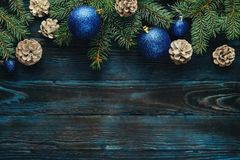 New Year and Christmas decorations Pine tree branches, cones, blue Christmas toys on a wooden background. Royalty Free Stock Photos