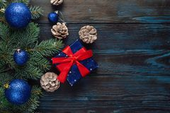 New Year and Christmas decorations Pine tree branches, cones, blue Christmas toys on a wooden background. Royalty Free Stock Images