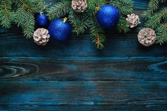 New Year and Christmas decorations Pine tree branches, cones, blue Christmas toys on a wooden background. Stock Photo
