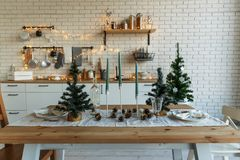 New Year and Christmas 2018. Festive kitchen in Christmas decorations. Candles, spruce branches, wooden stands, table. Laying royalty free stock images