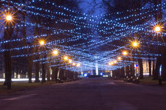 New Year and Christmas festoon illumination. On city alley Royalty Free Stock Photo